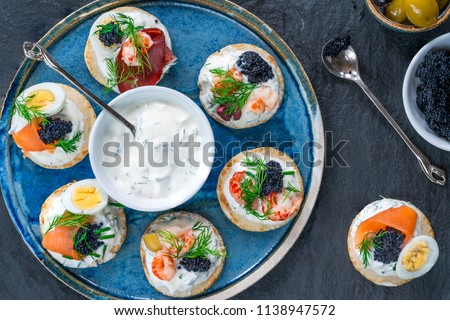 Selection of cocktail blinis with salmon, cured bresaola, crayfish, caviar, quail eggs and sour cream - gourmet party food - top view Stock photo ©