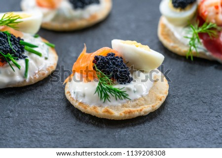 Selection of cocktail blinis with salmon, cured bresaola, crayfish, caviar, quail eggs and sour cream - gourmet party food  Stock photo ©