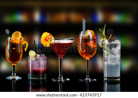 Selection of cocktails martini spritz bramble gin tonic bar blurred background