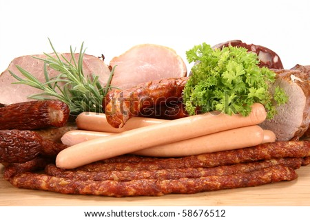 Selection of cold meat (ham, sirloin, headcheese, sausages, hot dogs) decorated with rosemary and parsley
