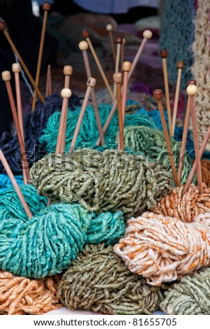 selection of colored wool with knitting needles