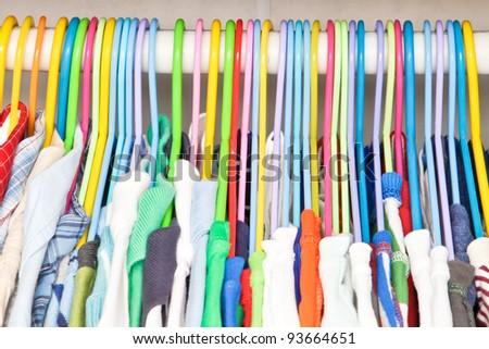 Selection of colorful clothes hanging in a wardrobe