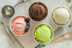 Selection of colorful ice cream scoops in paper cones, copy space