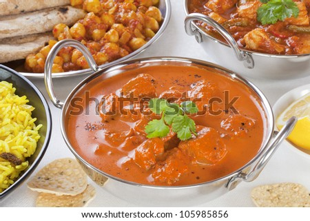 Selection of curry dishes with rogan josh, pillau rice,chana dhal,chicken jalfrezi and poppadums.