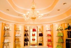 Selection of designer handbags on-shelf display in glamorous boutique.