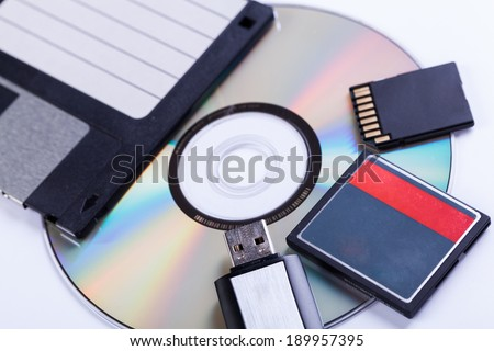 Selection of different computer storage devices for data and information including a CD-DVD, floppy disc, USB key, compact flash card and SD card viewed in a neat arrangement from overhead
