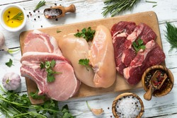 Selection of different meat at white wooden table. Chicken, beef and pork at cutting board. Top view.