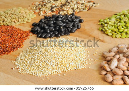 Selection of dry foods--red and white quinoa, lentils, peas, beans, and wild rice--on a cutting board