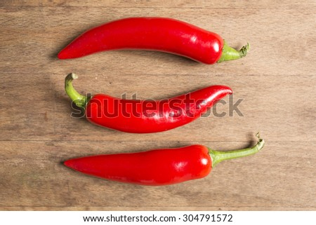 Selection of fresh red chilli on a wooden kitchen work surface