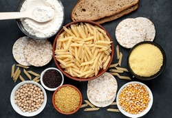 Selection of gluten free food. Chickpeas, bread, couscous, bulgur, pasta, bread, flour, quinoa on a stone background