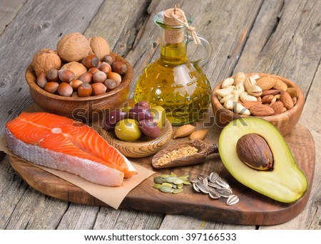 Selection of healthy fat sources on wooden table.