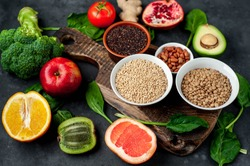 Selection of healthy food:  fruits, seeds, cereals, superfoods, vegetables, leafy vegetables on a stone background. Healthy food for humans