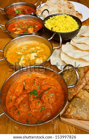 Selection of indian curries with pilau rice naan bread poppadoms and samosas a popular buffet choice