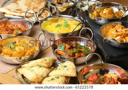 Selection of Indian food including curries, rice, samosas and naan bread. - stock photo