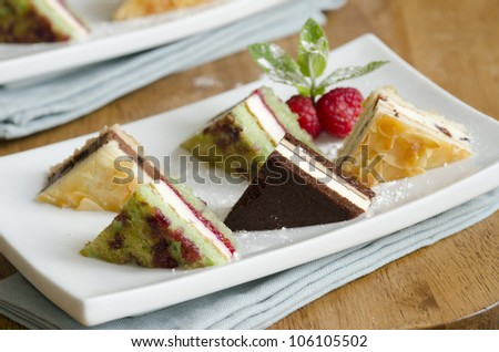 Selection of mini dessert sandwiches decorated with mint and raspberries