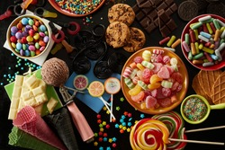 Selection of party treats for a kids birthday with assorted candies, ice cream , cookies, biscuits, chocolate bars, sprinkles and lollipops in an overhead view