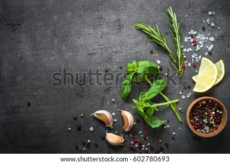 Selection of spices herbs and greens. Ingredients for cooking. Food background on black slate table. Top view copy space.