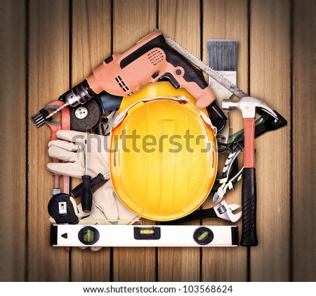 Selection of tools in the shape of a house, home improvement concept on old wood