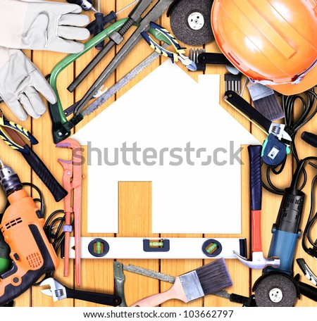 Selection of tools in the shape of a house on old wood