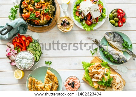 Selection of traditional greek food - salad, meze, pie, fish, tzatziki, dolma on wood background, top view #1402323494