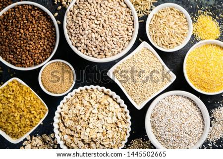 Selection of whole grains in white bowls - rice, oats, buckwheat, bulgur, porridge, barley, quinoa, amaranth on dark background #1445502665