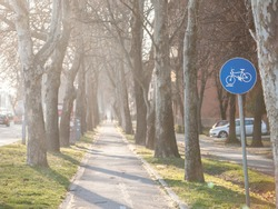 Selective blur on a european blue roadsign indicating the presence of a bicycle lane that is mandatory to be used by cyclists and other people using bike as a transportation.