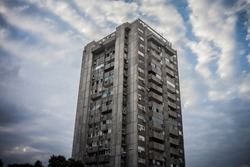 Selective blur on a High rise building from Novi Beograd, in Belgrade, Serbia, a traditional communist housing ensemble with a brutalist style, with a moving sky effect in background.