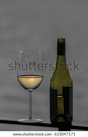 Selective color white wine on seaside deck rail with bottle