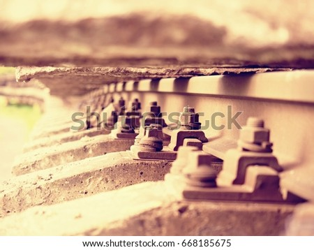 Selective field of focus. Detail of rusty screws and nut on old railroad track. Concrete tie with rusty nuts and bolts. Damaged surface of rail rod. No train passed this railroad for a long time.