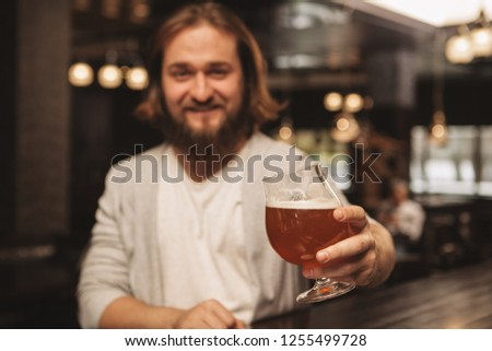 Selective focs on a glass of delicious craft beer in the hand of cheerful bearded man. Male customer enjoying weekend, having beer at local pub, copy space. Recreation, consumerism concept
