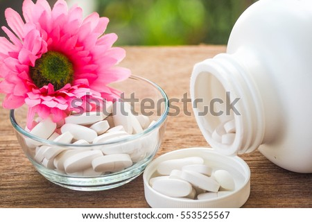 Selective Focus A Calcium white tablet a good supplement pills for woman bone in Healthy care Concept: decorated with pink flower