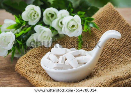 Selective Focus A Calcium white tablet a good supplement pills for woman bone in Healthy care Concept: decorated with white flower on sack bag.