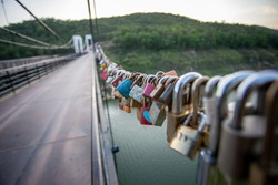 selective focus a lot of different love padlocks on hemp rope Locks left by people in love, a symbol of eternal love. Pine suspension bridge in Thailand.