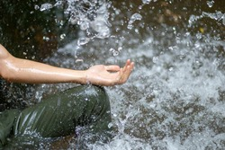 selective focus, a man's hand, supports the water beside the waterfall Gives a refreshing feeling of moisture And natural sensations, waterfalls and small streams in Thailand in the summer