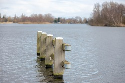 Selective focus a row of mooring poles in the Dutch canal, Wooden jetty and bollard in river shore near the bridge.