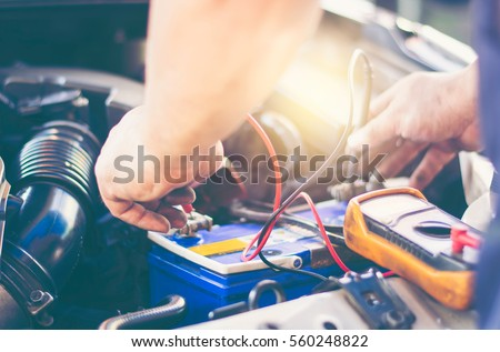 Selective focus an auto mechanic uses a multimeter voltmeter to check the voltage level in a car battery.