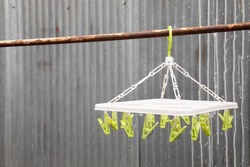 Selective focus and close up shot with copy space of cloth hanger with clips in the house on blurred background of grunge wavy zinc roof shows the concept of people surround by many friends.