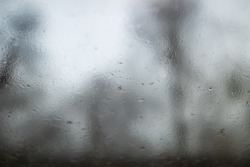 Selective focus and macro view of droplet of water, dew or stream on glass of window, and background of dim, foggy, hazy environment with blurry outer tree.