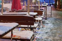 Selective focus and night view, red and white caution tape wrapped around outdoor tables and seats area of cafe which covered by snow and closed by lockdown during epidemic COVID-19 in winter season.