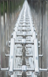 Selective focus and perspective view of chrome, shiny metal fence which is made of aluminum tube chain shows beautiful pattern and reflection from the smooth surface. It is an abstract art for modern.