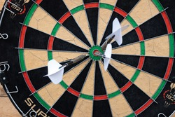 selective focus, arrows with white feathers stuck in the center of the dart board. copy space.