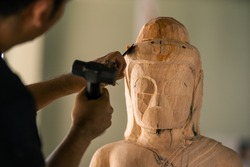 Selective focus. Asia craftsman professional carving buddha statue with chisel in workshop. Artist engrave wood. Carpentry woodwork. Handcraft carved.