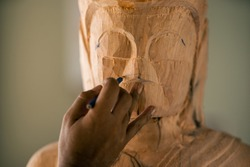 Selective focus. Asia craftsman professional   use pencil draft on face buddha statue for craving in workshop. Artist engrave wood. Carpentry woodwork. Handcraft carved.