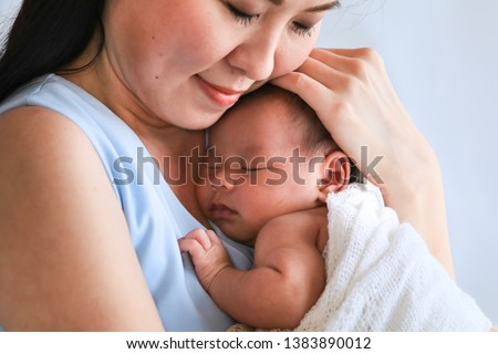 Selective focus Asian beautiful mother hold newborn baby 0-1 month in her arm with love and gently, newborn baby happy sleeping in mother arm , newborn baby feeling secure while sleeping in mother arm