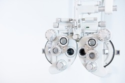 Selective focus at Optometry frame equipment. With blurred white background for copy space. Optometrist tool to examine eye visual system of patient with professional machine before made glasses.