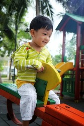 Selective focus at the Asian little boy / Little boy playing carousel in the playground.