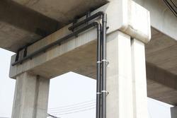 Selective focus, black drainage pipe installed under sky train concrete bridge in Bangkok, Thailand. Drainage pipe system, concrete bridge, texture, train bridge, construction, concrete beam concept.