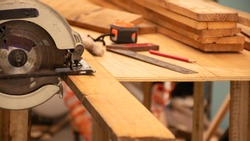 Selective focus. Carpenter is cutting plank by electronic saw. Blurred background is pile of wood , measuring tape (steel tape) , pencil and L ruler. Background with copy space.