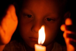 Selective focus. Child with sad eyes looks at flame of burning candle in dark. Concept of memories or mourning for dead. Religious sacrament in church. Kid close fire with hands and warm. Toddler face