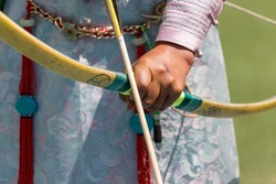 Selective focus close up of an arrow and the hand of a Mongolian lady archer holding a bow and wearing cultural national dress on the Archery Field at the Naadam Festival in Ulaanbaatar in Mongolia